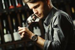 Bokal del vino rojo en el fondo, sommelier masculino que aprecia la bebida imagen de archivo