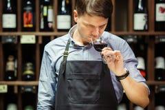 Bokal des Rotweins auf Hintergrund, männlicher Sommelier, der Getränk schätzt Stockfotografie