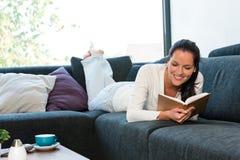 Bokar liggande läsning för den unga kvinnan soffasofaen Arkivfoton
