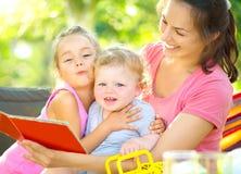 bokbarn henne moder som läser till Arkivfoto
