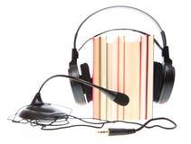 Bokbunt och hörlurar med mikrofon med en isolerad mikrofon Fotografering för Bildbyråer