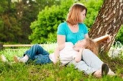 bokdotter henne moder som läser till Arkivfoto