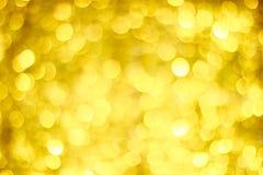 Bokeh金黄迷离 金闪烁的光 抽象背景bokeh盘旋defocused 免版税库存照片