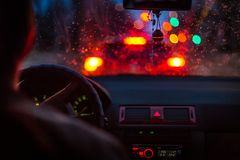 Bokeh从交通堵塞点燃通过一扇汽车挡风玻璃在多雨夜在大城市 免版税库存图片