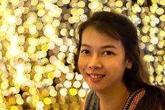 bokeh光背景的年轻亚裔妇女 免版税库存图片