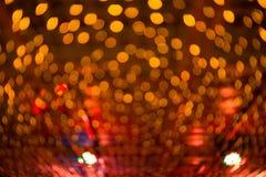 Bokeh点燃,在橙色抽象背景的闪烁迷离斑点光 库存图片