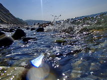 Bokeh резюмирует предпосылку преднамеренно из фокуса, или defocused падая брызг моря против голубого неба Стоковые Фото