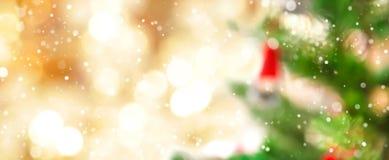 Bokeh рождественской елки и золота нерезкости с снегом Стоковая Фотография