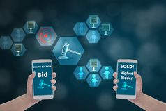 Женский смартфон удерживания руки для того чтобы вписать цену для заявкы, через беспроводную сеть на голубой предпосылке bokeh со стоковые изображения rf