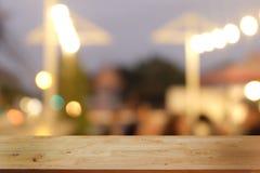 Пустой темный деревянный стол перед абстрактной запачканной предпосылкой bokeh ресторана стоковое фото