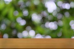 Пустой темный деревянный стол перед абстрактной запачканной предпосылкой bokeh ресторана стоковое изображение