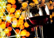 反对金黄bokeh的两块红葡萄酒玻璃点燃背景 免版税图库摄影