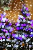 在圣诞树的抽象轻的bokeh与雪剥落 免版税库存照片
