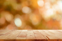 在棕色bokeh摘要背景的木台式 库存照片