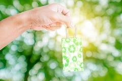 递举行一点小包绿色回收纸袋,在绿色Bokeh和明亮的黄灯背景 免版税库存图片