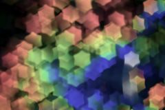 Bokeh, abstract colorful background of defocused hexagon stars. Festive pale pink decoration.  royalty free stock photography