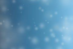 Bokeh abstracto de la nieve del invierno en fondo de la falta de definición del cielo azul Imágenes de archivo libres de regalías