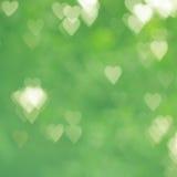 Bokeh abstrato do coração do verde do fundo fotografia de stock