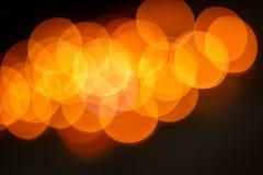 Bokeh anaranjado en fondo oscuro Foto de archivo libre de regalías