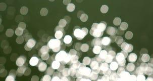 Bokeh astratto dei cerchi bianchi della riflessione di Sun sopra acqua archivi video