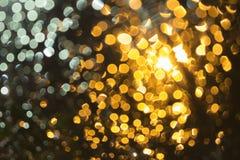 Bokeh astratto: Luce del fondo vaga, arancio dalle goccioline di acqua, parte anteriore dell'automobile fotografie stock