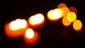 Bokeh av röda stearinljus inom en europékyrka arkivfilmer