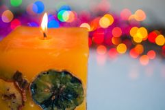 Colored candle burning against the background of new year lights bokeh stock photo