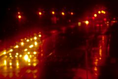 Bokeh background of trafic lights reflecting on white surface at night. Bokeh background of orange and yellow trafic lights at night, reflecting on wet surface stock images