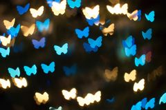 Bokeh background with unique butterfly shaped  lights or blurred lights background. Butterfly blurred lights in various shades of blue,green, teal, red, yellow Stock Photo