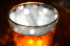 Bokeh beer. Glass of beer with shiny bokeh on dark background Stock Photography