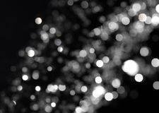 Bokeh on black. Bokeh lights on black background, shot of flying drops of water in the air Stock Photo