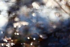 Bokeh borrou reflexões da água azul Fotos de Stock