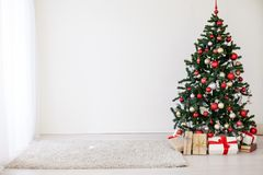 Christmas tree with red gifts in the white room Christmas Stock Images
