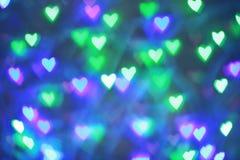 Bokeh colorido das festões na forma do coração usada como o fundo para o dia de Valentim fotos de stock royalty free