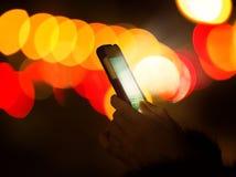 Bokeh colorido de la luz de la noche de la pantalla del teléfono elegante de la mano de la mujer que brilla intensamente Imagen de archivo