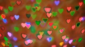 Bokeh colorido de las guirnaldas del centelleo en la forma del corazón usado como fondo para el día de tarjetas del día de San Va almacen de video