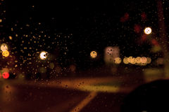 Bokeh da noite, chuva Pingos de chuva em uma janela com fora do estreptococo do foco Foto de Stock Royalty Free