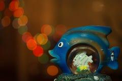Bokeh da noite Peixes azuis da estatueta com círculos de incandescência coloridos do bokeh na noite fotografia de stock