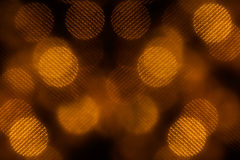 Bokeh dark orange mesh circles on black background. Royalty Free Stock Photo