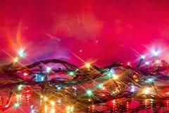 Bokeh das festões coloridos de incandescência do Natal refletidas Imagens de Stock Royalty Free