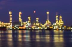 Bokeh de la refinería de petróleo en el crepúsculo junto con la reflexión del río Foto de archivo
