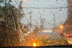 Bokeh de las gotas de agua y de la luz de calle en la noche en el escudo de viento del coche durante tormenta fotos de archivo libres de regalías
