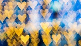 Bokeh de luzes alaranjadas mornas em fundo defocused numa forma dos corações Fotos de Stock Royalty Free