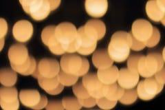 Bokeh de oro en un fondo negro, contexto oscuro abstracto con las luces calientes defocused Imagen de archivo libre de regalías
