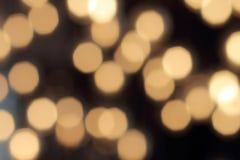 Bokeh de oro en un fondo negro, contexto oscuro abstracto con las luces calientes defocused Fotos de archivo libres de regalías