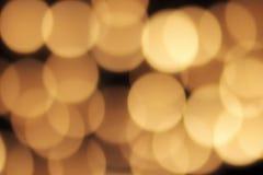 Bokeh de oro en un fondo negro, contexto oscuro abstracto con las luces calientes defocused Fotografía de archivo