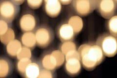 Bokeh de oro en un fondo negro, contexto oscuro abstracto con las luces calientes defocused Foto de archivo libre de regalías