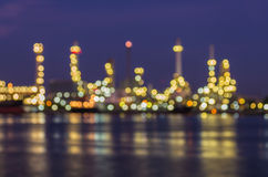 Bokeh de raffinerie de pétrole au crépuscule avec la réflexion de rivière photo stock