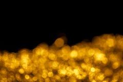 Bokeh del oro en negro con el espacio para el texto Fotos de archivo