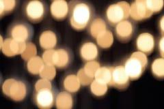 Bokeh dourado em um fundo preto, contexto escuro abstrato com luzes mornas defocused imagens de stock
